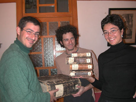 Silvia Pugliese holding 4 small books and Nikolas Sarris and Marco di Bella holding 1 huge book