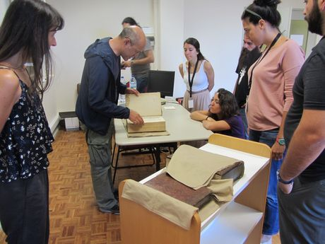 The participants examining a book with George Boudalis